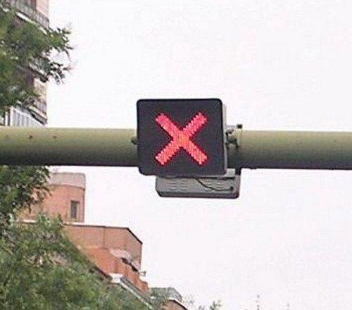 Si usted circula por un carril y se enciende una luz roja en forma de aspa, ¿qué debe hacer?