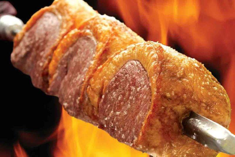 ¿En qué estado se prepara el churrasco sobre una base de sal gruesa y harina de mandioca y se asa insertado en pinchos?