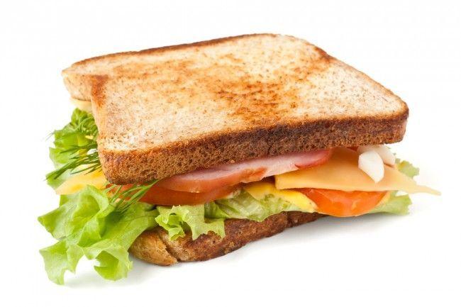 Un sandwich de jamón, queso, lechuga y tomate